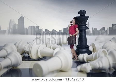 Businesswoman Leaning On A Chess Queen