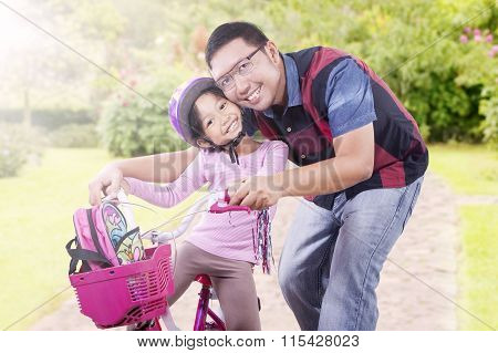 Cheerful Girl And Dad With Bicycle At The Park