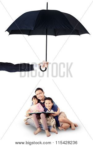 Children And Dad Reading Book Under Umbrella