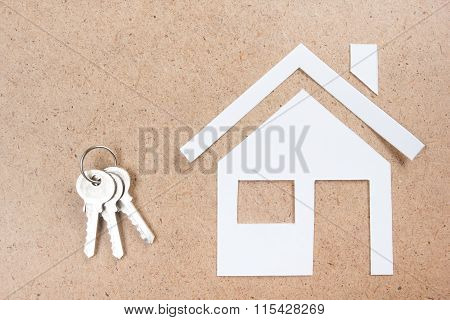 Silver key with house figure and on wooden background. Real Estate. Top view.
