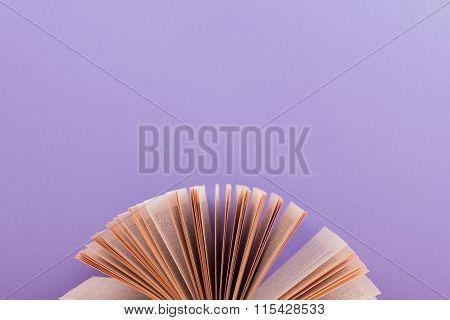 Open book on purple artistic bavkground.