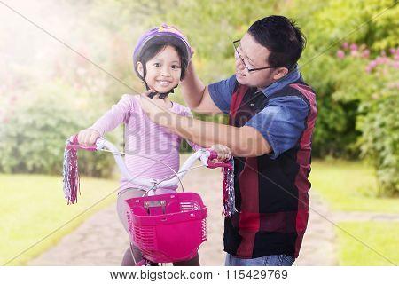 Dad Fastens Helmet On His Daughter