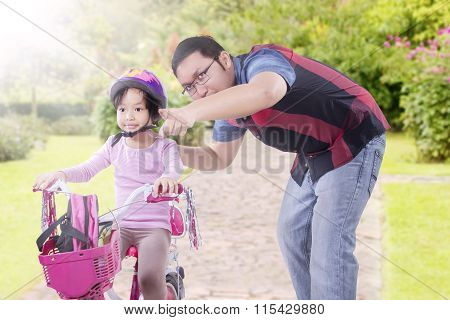 Dad Teach Daughter To Ride Bicycle At The Park