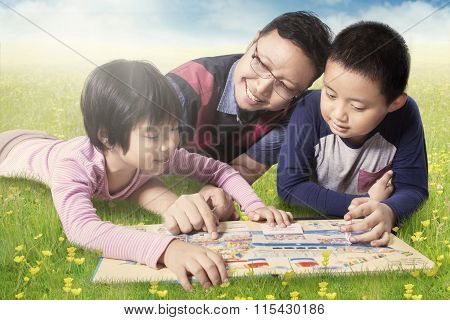 Family Reading Book While Lying On Meadow