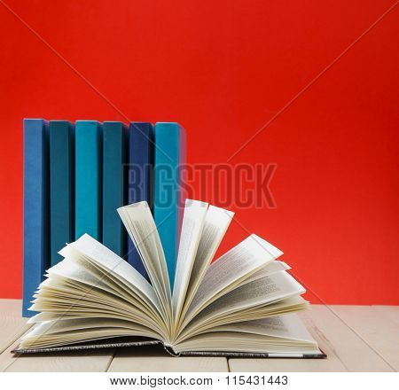 Hardback books, diary, fanned pages on wooden deck table and red background.