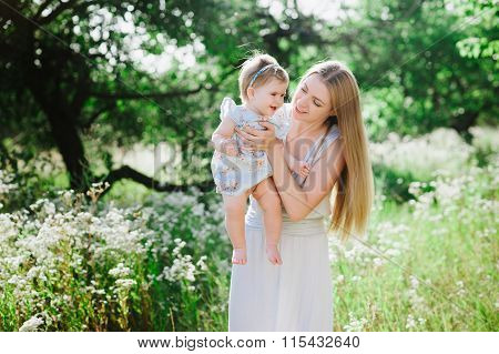Young mother playing with her little daughter on the nature