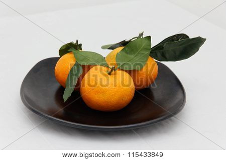 Mandarines On A Black Plate.