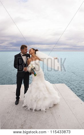 Groom and bride are having fun by the sea line.