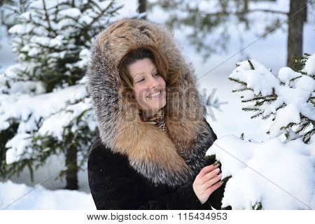 Positive middle-aged woman in  fur coat at  winter park
