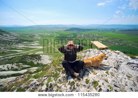 Woman And Dog Sitting On Top Of A Cliff .
