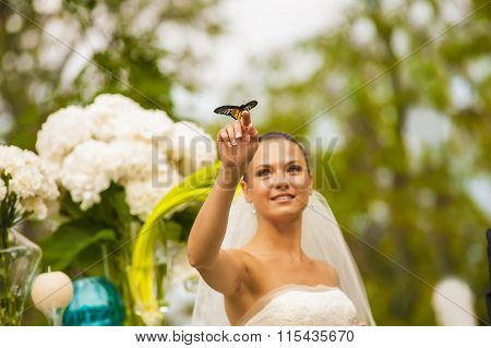 The bride is holding butterfly on her finger.