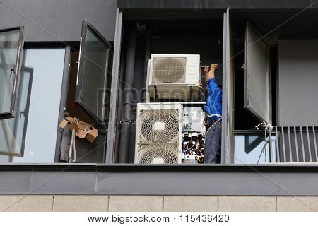 Man Fixing And Mounting Air Conditioning