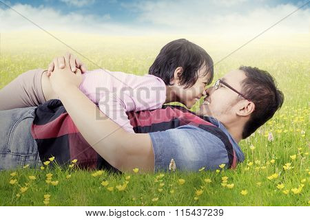 Joyful Girl And Dad Kissing Nose On Meadow