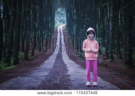 Little Girl Standing In The Pine Forest