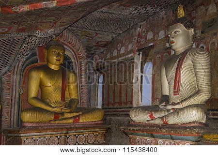 Two ancient statues of seated Buddha in ancient Buddhist cave temple. Sri Lanka