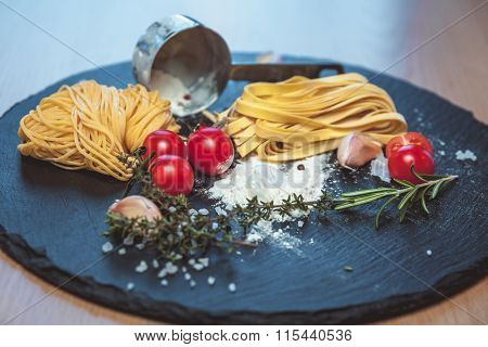 Beautiful Fresh Spaghetti On The Blackboard With Spices And Tomatoes
