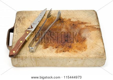 Knife And Tongs On A Wooden Chopping Board Isolated On White Background
