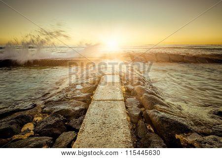 walkway to the ocean in sunset.