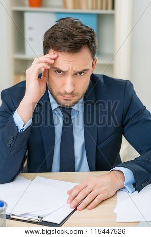 Emotional office worker sitting at the table