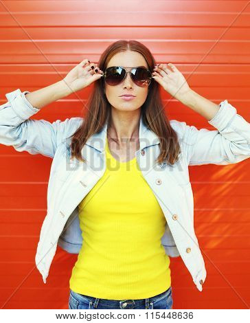 Pretty Young Woman In Sunglasses And Jeans Jacket Over Orange Background