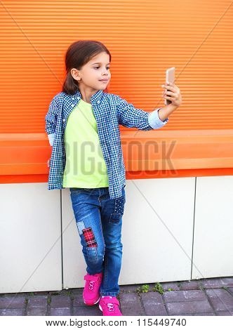 Happy Little Girl Child Taking Picture Self Portrait On Smartphone In City Over Colorful Background