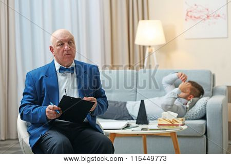 Young man lying on sofa on reception at psychologist