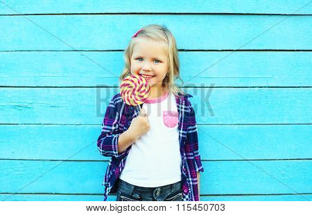 Happy Smiling Child With Sweet Caramel Lollipop Having Fun Over Colorful Blue Background