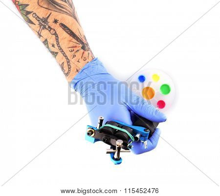Tattooist hands in blue gloves with tattoo machine and colourful inks isolated on white background, close up