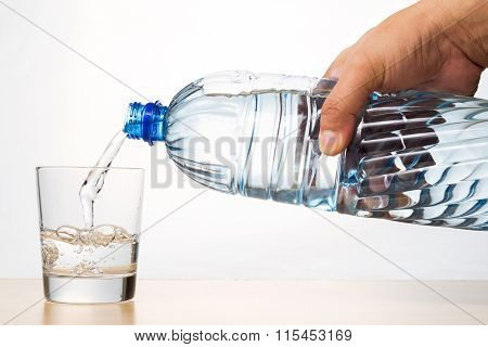 Hand Pouring Refreshing Natural Mineral Water From Bottle Into Glass