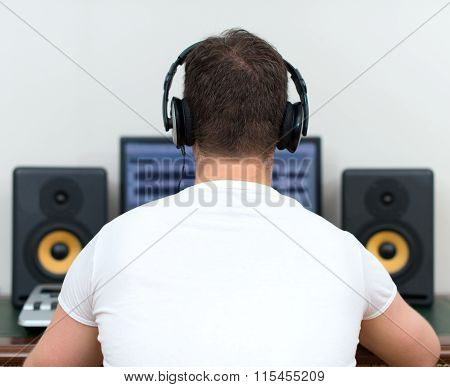 Male sound producer in recording studio. Back view. Space for your text.