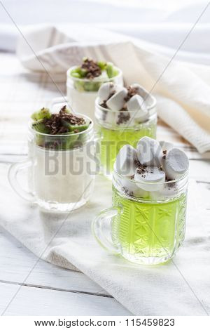 Jelly with kiwi fruit with marshmallows and grated chocolate in glass