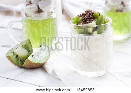 Vanilla panna cotta with kiwi and grated chocolate in glass, sliced kiwi on white wooden table