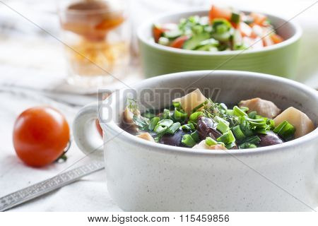 Vegetable soup with beans and chicken, fresh herbs in a clay pot