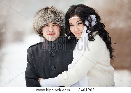 Beautiful wedding couple, asian bride and groom embraced. Young man in winter coat, fur hat, lady we