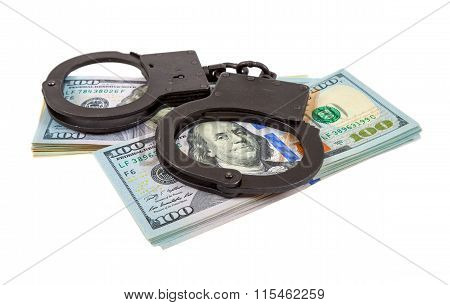 Steel Handcuffs Lying On A Stack Of Dollar Bills On The White Background