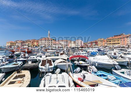 ROVINJ CROATIA - JULY 2 : A large group of boats anchored in the marina with a view of the city promenade and the old city core on July 2 2015 in Rovinj Croatia.