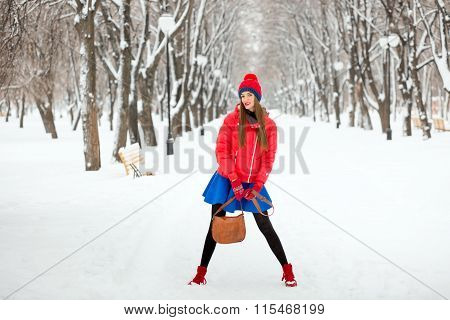 Beautiful Winter Portrait Of Young Woman In The Winter Snowy Scenery. The Girl In A Red Hat, A Red J