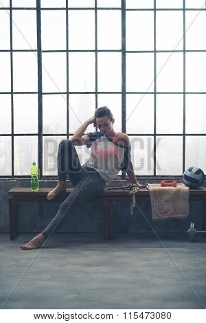 Pensive Woman In Workout Gear Resting On Bench In Loft Gym