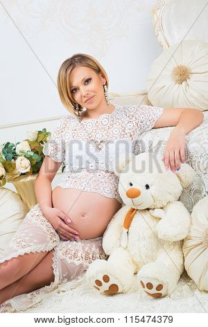 Young Pregnant Woman  Sitting Near White Sofa With Teddy Bear