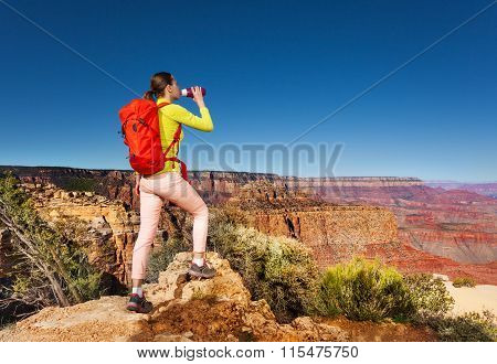 Hiker drinks water stand on edge of Grand canyon
