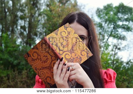 Shy brunette woman hiding behind a notebook
