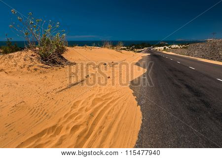 Asphalt road with sandy dunes. Mui Ne town area, Vietnam