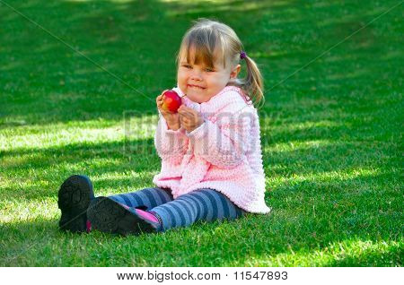 Beautiful little girl holding an apple