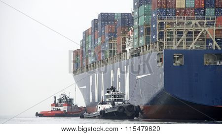 Multiple tugboats push CMA CGM LYRA sideways through the fog to the dock at the Port of Oakland