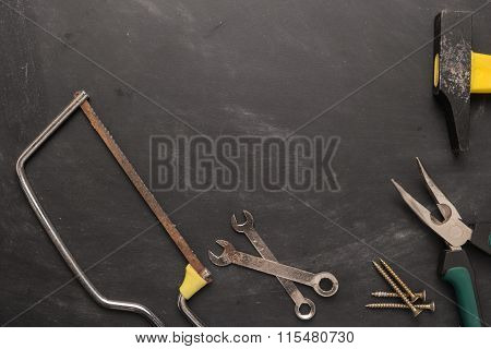 Set Of Saw, Plier, Screw And Hammer. Tools Over A Wood Panel. Top View With Copy Space.