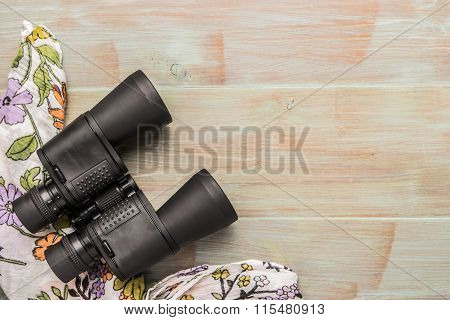 Travel, Summer Vacation, Tourism And Objects Concept - Close Up Binoculars And Scarf On Wooden Table
