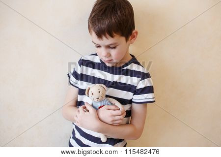 boy hugging a teddy bear