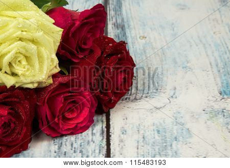 Five Roses  On A Background Of A Wooden Tabletop In A Vintage Style