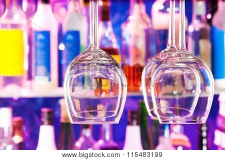 Some wine glasses on hanger in bar