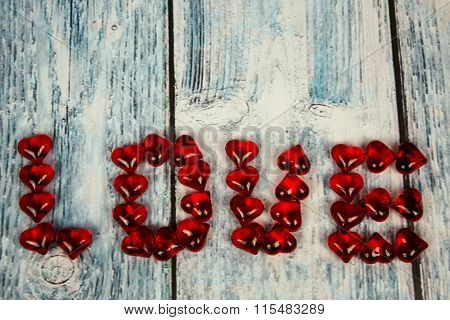 The Word Love Arranged With Red Hearts On A Wooden Background